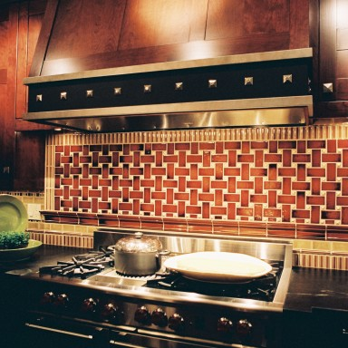 "This bespoke hood fan was created to integrate seamlessly with the shaker cherry cabinets. The addition of black metal and white bronze reinforces the craftsman aesthetic and works with the bronze Rocky Mountain hardware. An intricate, handcrafted, ceramic tile back-splash was designed and created especially for this space above the 48"" Wolf range."
