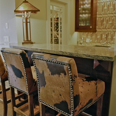 Bespoke hide bar stools with nail head detail work perfectly in this play space. The craftsman style handcrafted back-splash tile is a great focal point that is flanked by custom cherry cabinets. A custom wine storage room was created to the owner's specifications to house his favorite wine. The lighting is by Hubbarton Forge and Fine Art Lamps.