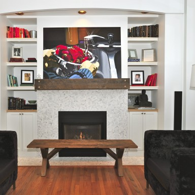 White on white on soft grey creates an open, expansive feel in this great room. This fabulous fireplace focal point warms the room with the bespoke, reclaimed barn beam mantel and wooden bench. Cararra marble mosaic surrounds the firebox with custom shelving. The chairs are custom and the lamp purchased.