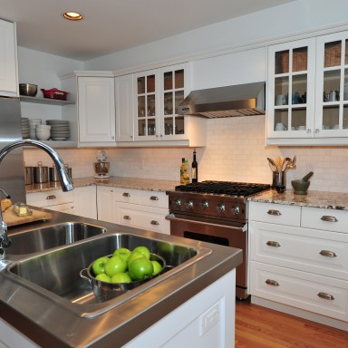 Re-designed, this layout becomes a functional work space for a professional chef. Custom stainless island counter-top and shelving was created to fit perfectly into the space. Professional Viking appliances suit this restauranteur's sensibilities in her personal kitchen. Cookbook tower and a pull-out pantry maximize storage in a smaller kitchen while the white and grey granite counter-top and white back-splash help the kitchen feel more expansive.