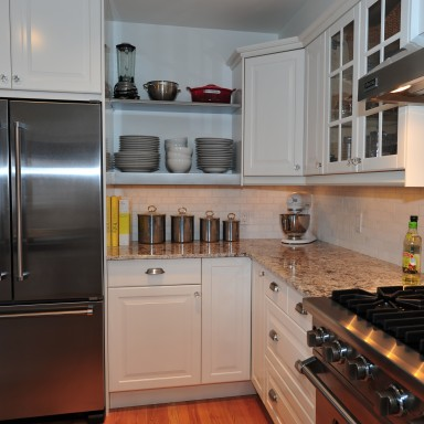 Custom stainless shelving houses this chef's dishes while the Viking appliance package is luxurious in it's professional attitude. A white and grey granite counter-top with Carrara marble subway tile back-splash integrates perfectly with the stainless surfaces.